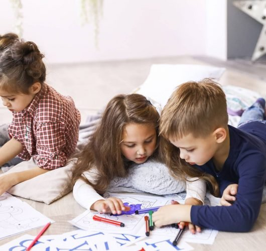 Consent Orders Parenting Mediation Three focused children are playing on the floor and drawing in coloring books